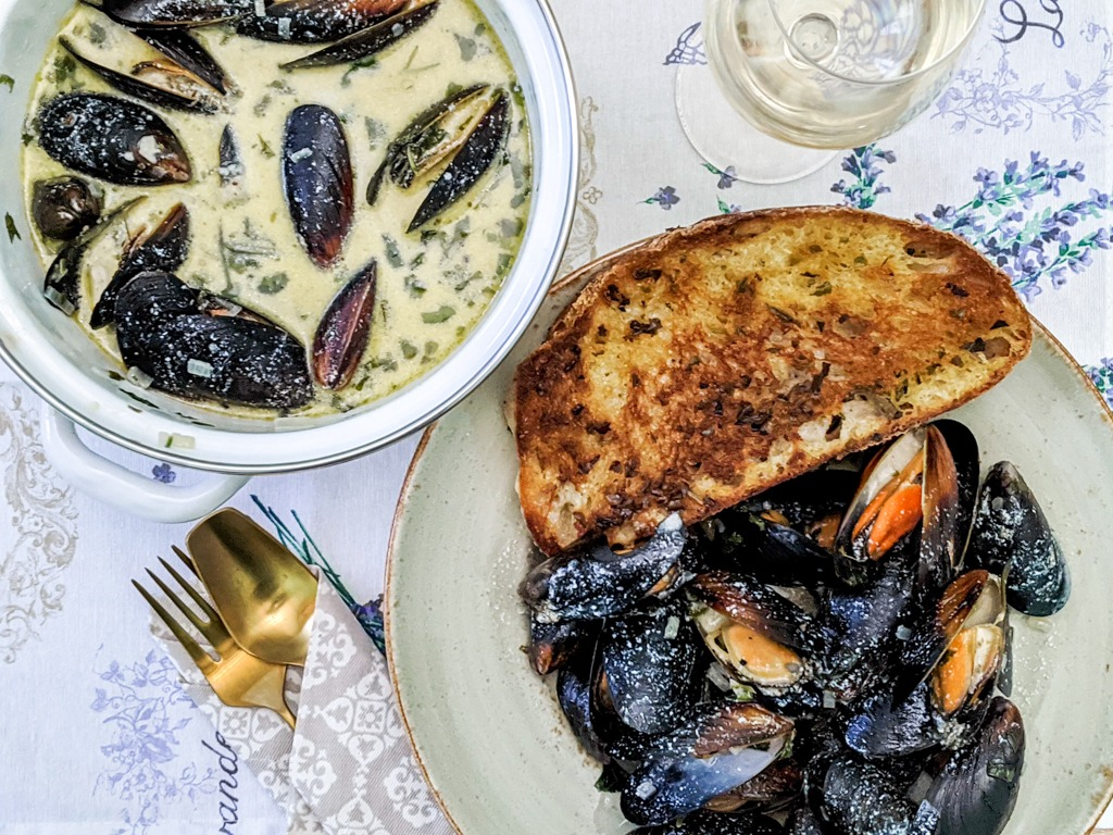 moules au roquefort or in English mussels in roquefort blue cheese sauce. Served with a glass of wine