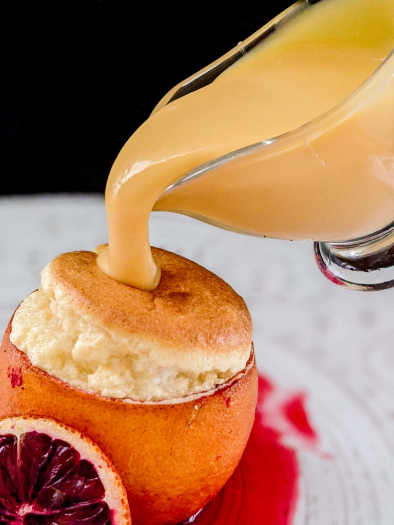 Blood Orange Creme Anglaise being poured into the blood orange Cointreau souffle