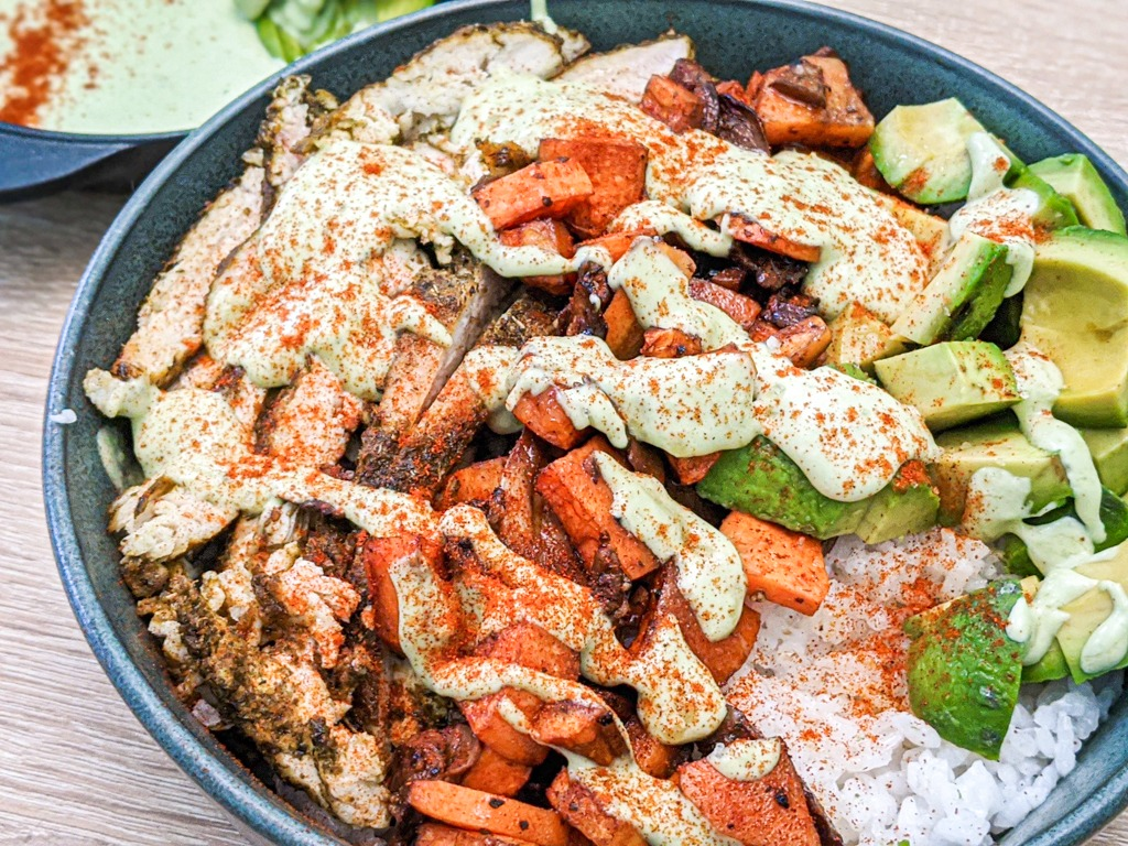 buddha bowl with khmeli suneli chicken, roasted balsamic veggies and rice. Topped with an avocado tahini sauce