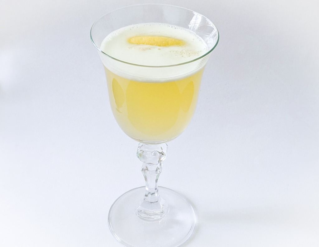 The Bees Knees classic cocktail with a lemon peel garnish. Served in a nick and nora glass