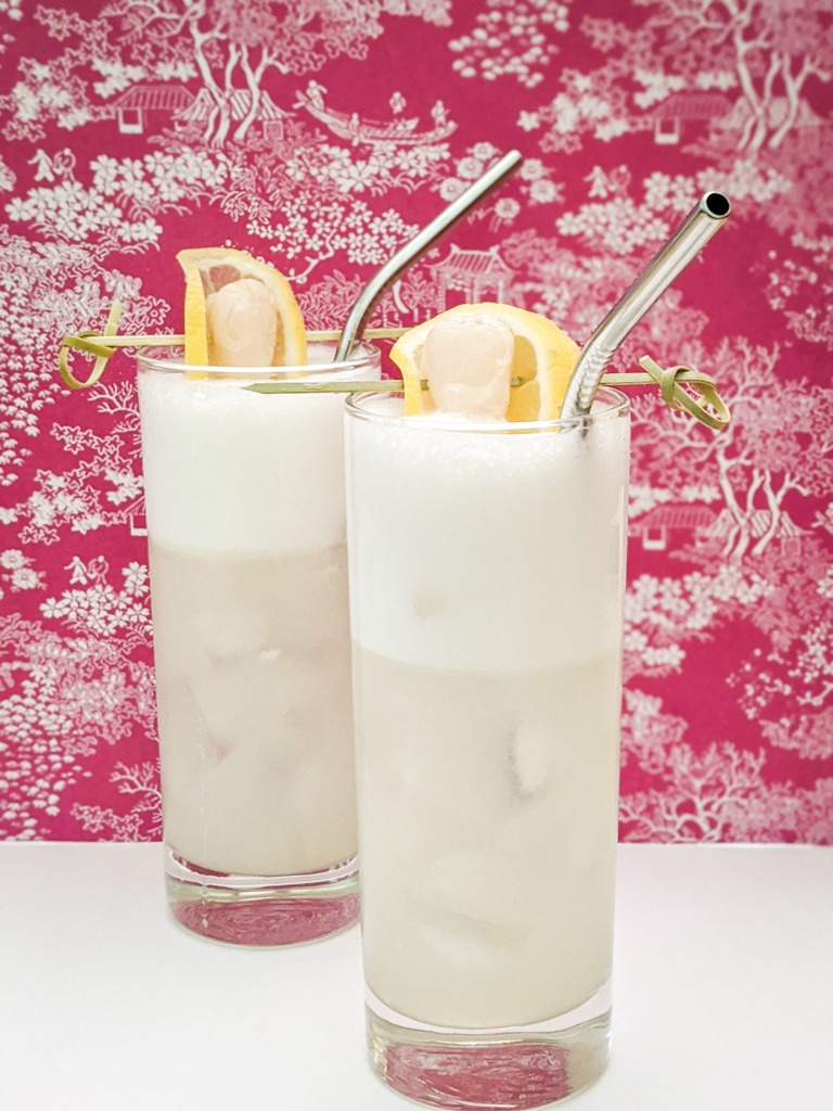 Japanese silver gin fizz cocktail with lemon wheel and lychee fruit garnish