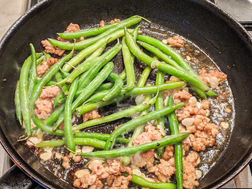 stir frying the string beans with pork and garlic