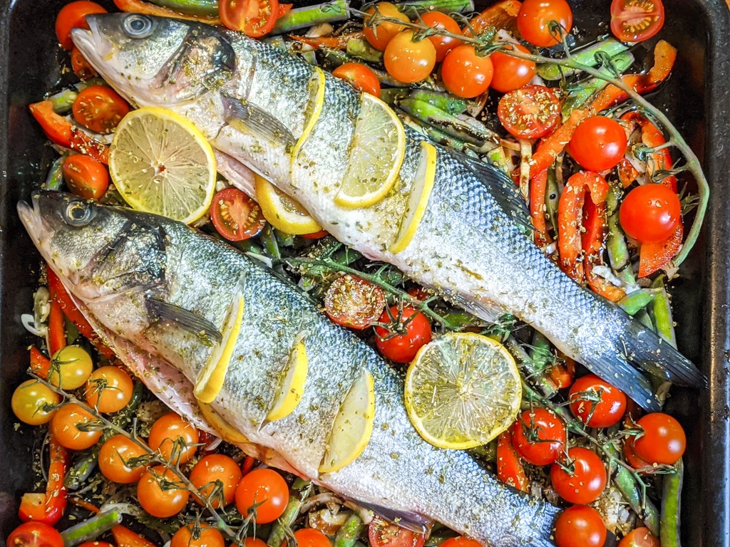 whole sea bass on a bed of fresh vegetables and tomatoes