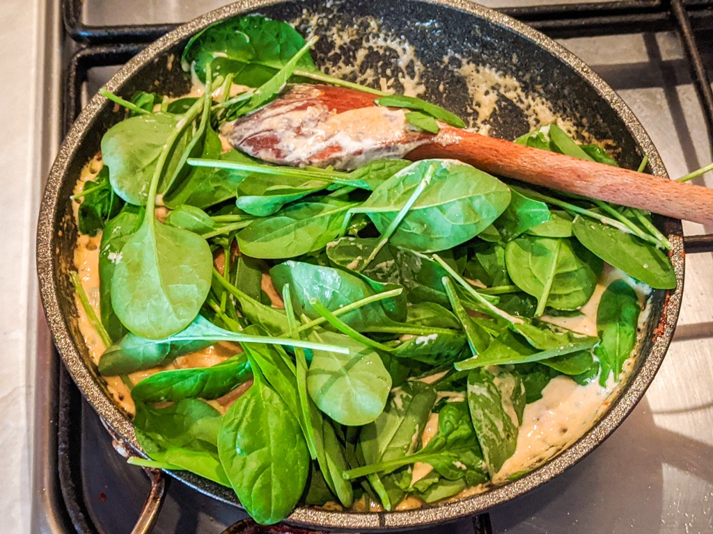 adding spinach to the Tequila Chicken Penne Pasta sauce