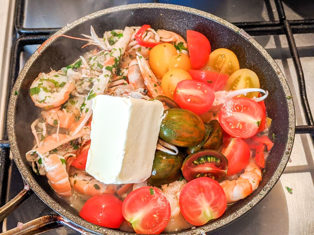 adding butter and tomatoes to the pasta all'amalfitana