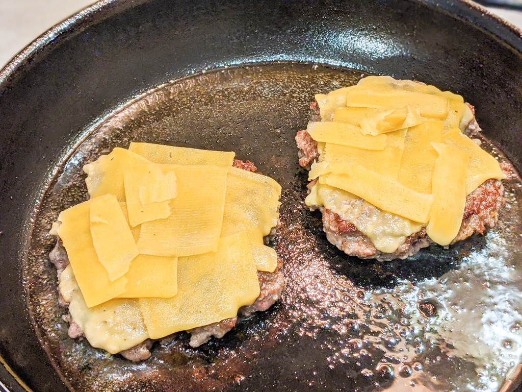 Placing trappista cheese on the burger patties