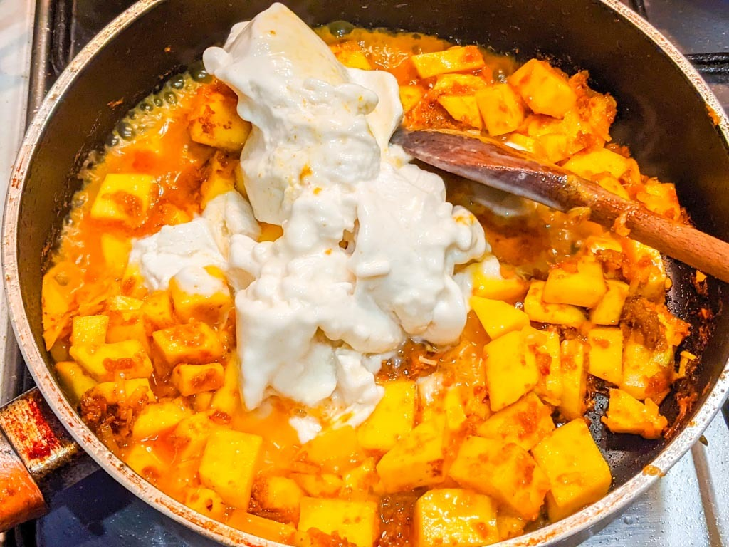 adding thick coconut milk to the pan for the curry