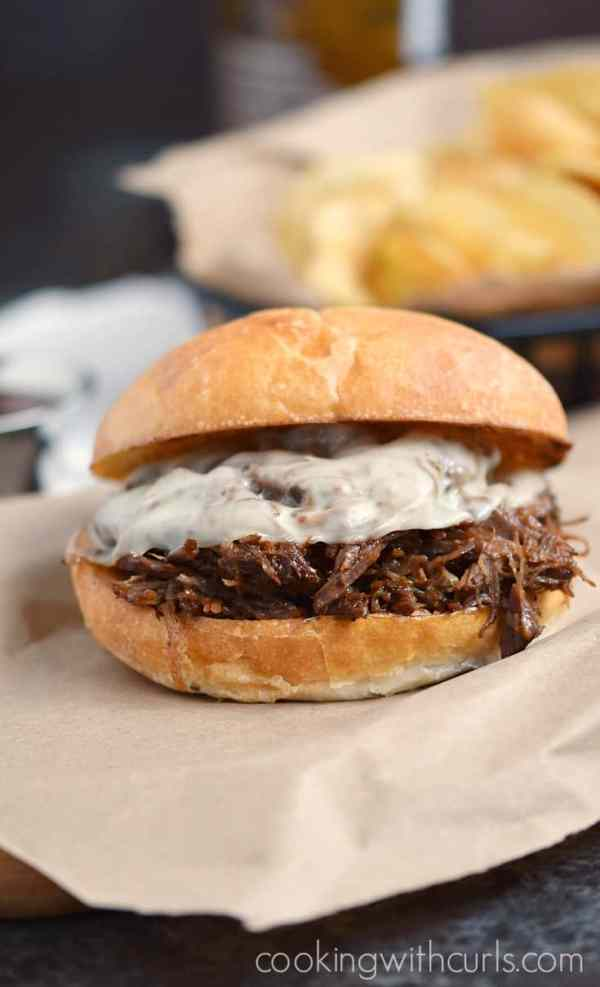 barbecue beef sandwich with melted cheese and potato chips on the side