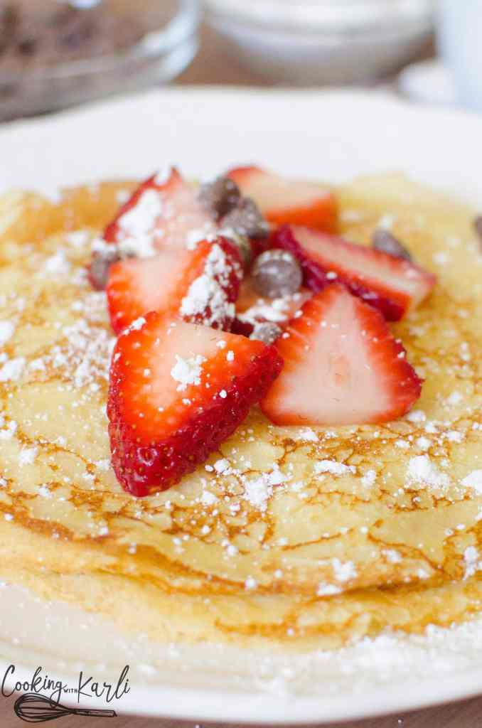 Strawberries, chocolate chips and powdered sugar piled high on a stack of crepes.
