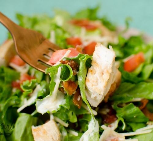 chicken, bacon, tomato and cheese in a green garden salad.