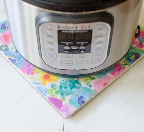 DIY hot plate made from a tile and scrapbook paper makes the perfect Instant Pot stand.