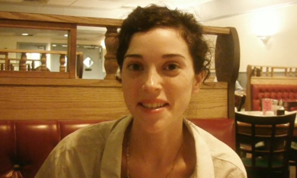 St. Vincent's Annie Clark sitting in a restaurant booth