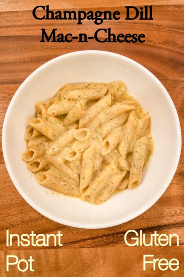 champagne dill macaroni and cheese made in an instant pot with gluten free pasta, sitting on a large wood cutting board