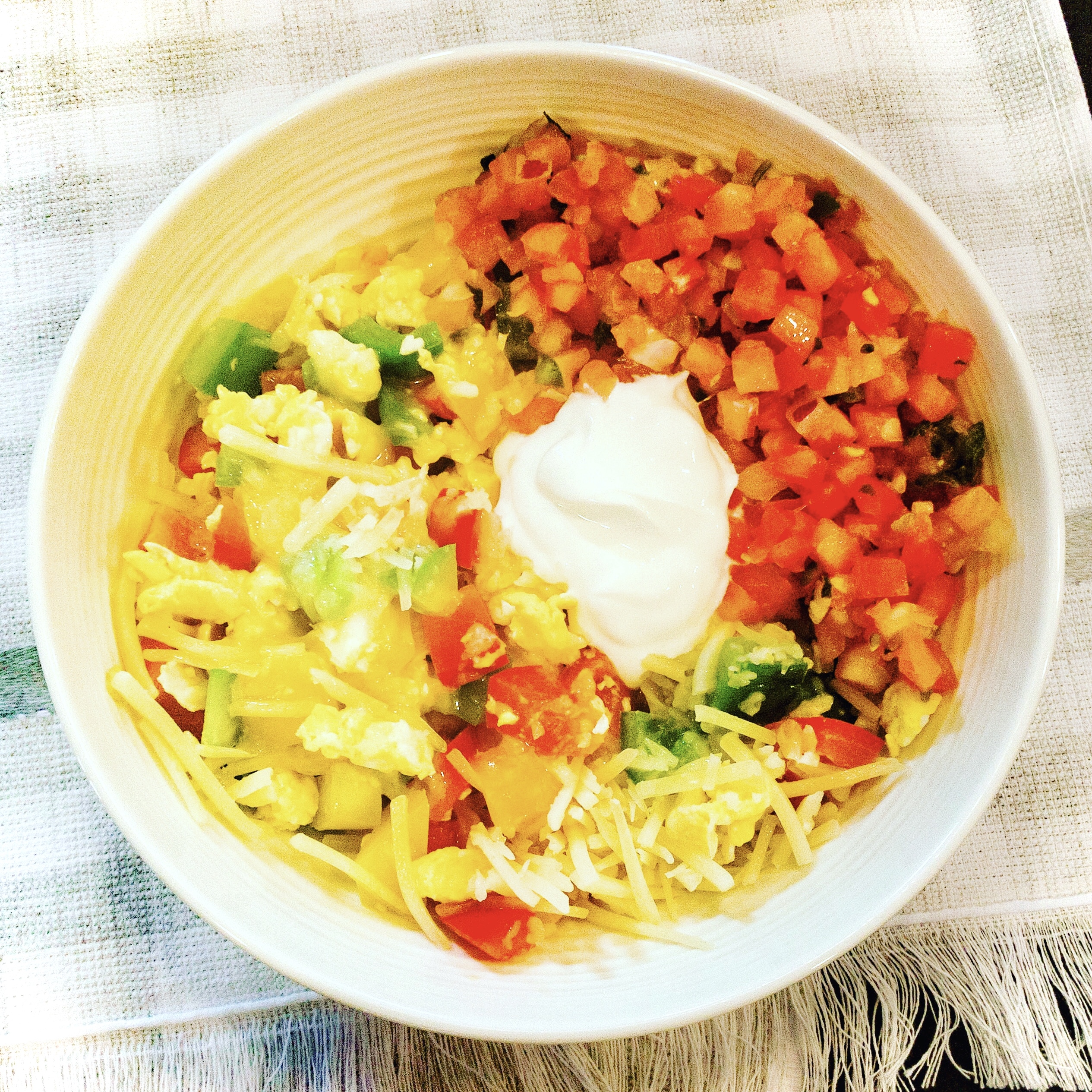 bowl of scrambled eggs, peppers, onions, pico, melting shredded cheese, and sour cream
