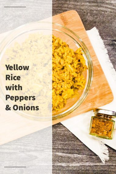 Yellow rice with peppers and onions, in a clear bowl on a cutting board, on top of a white napkin, sitting next to a container of turmeric on a dark wood table with this white shiplap wall