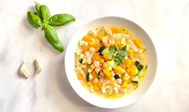 Italian Chickpea Soup in a bowl with fresh basil and garlic cloves on the side