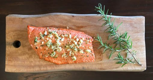 Baked Wild Salmon on wood plank with rosemary sprig