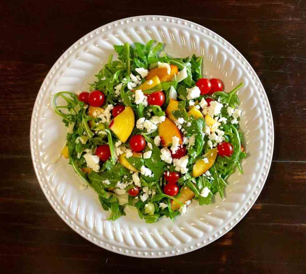 arugula, fennel, and nectarine salad on fancy white plate