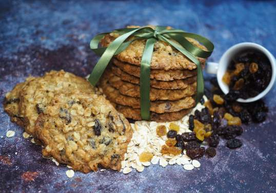 Chewy-oatmeal raisin cookies on a grey cement work surface adorn with oatmeal flakes and raisins on the sides.
