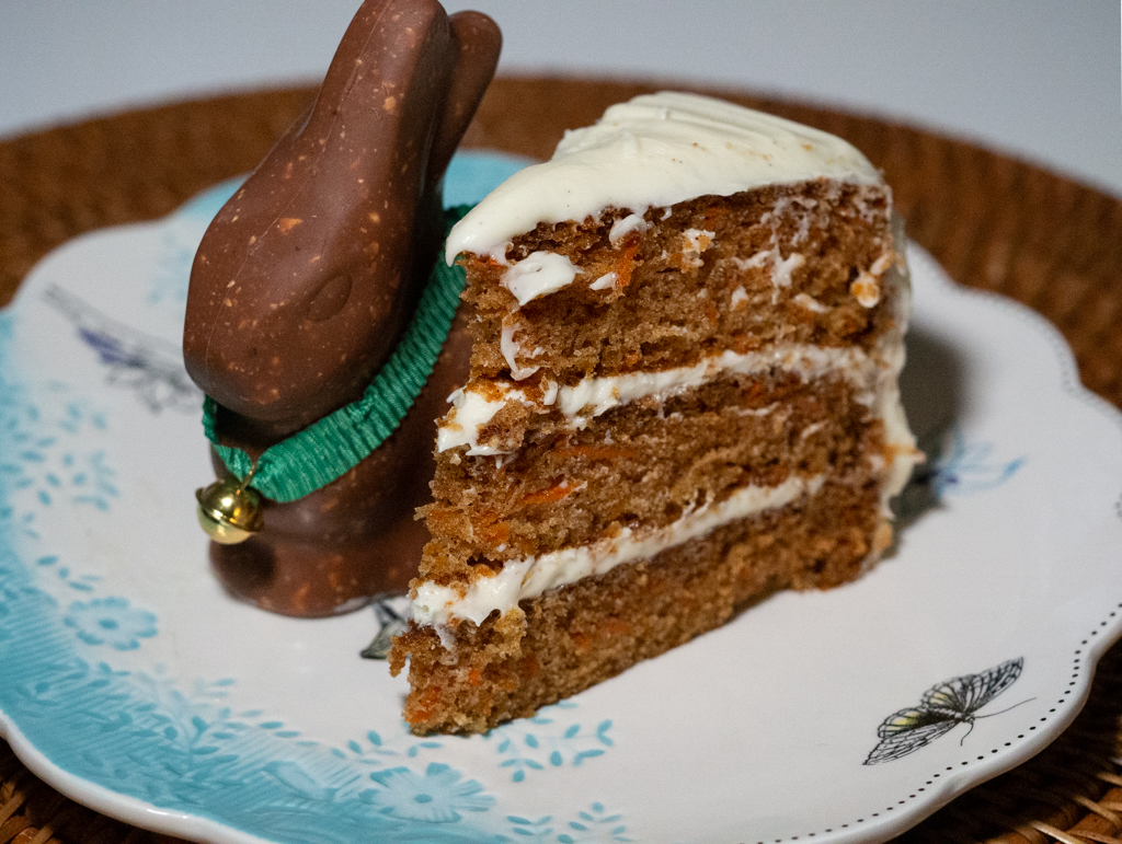 A slice of carrot cake in a dessert plate with chocolate bonny in the side