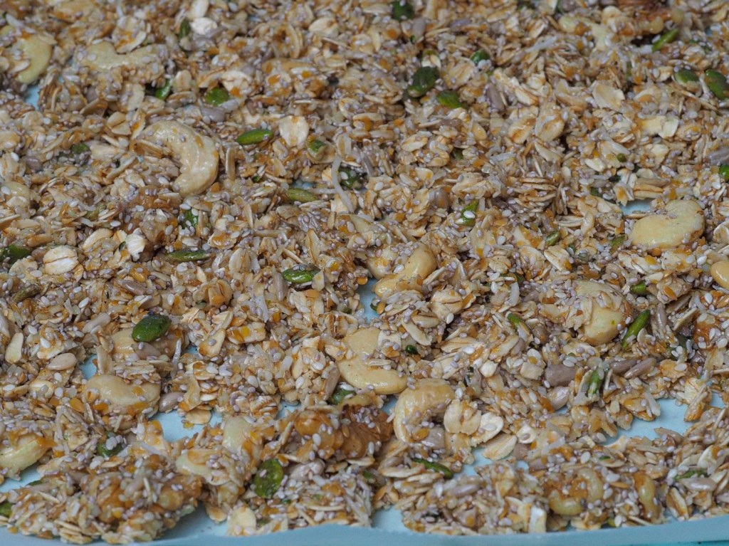 A mix of granola ingredients spread on a blue baking sheet