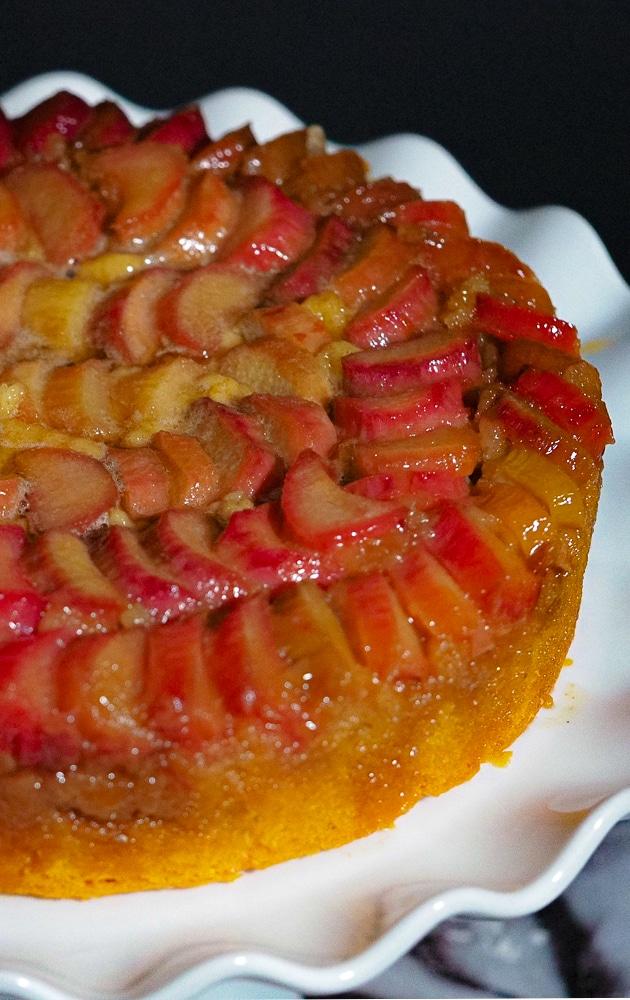 Rhubarb upside-down cake in a white cake stand