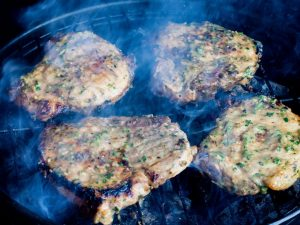 Grilling pork chops on a charcoal bbq grill