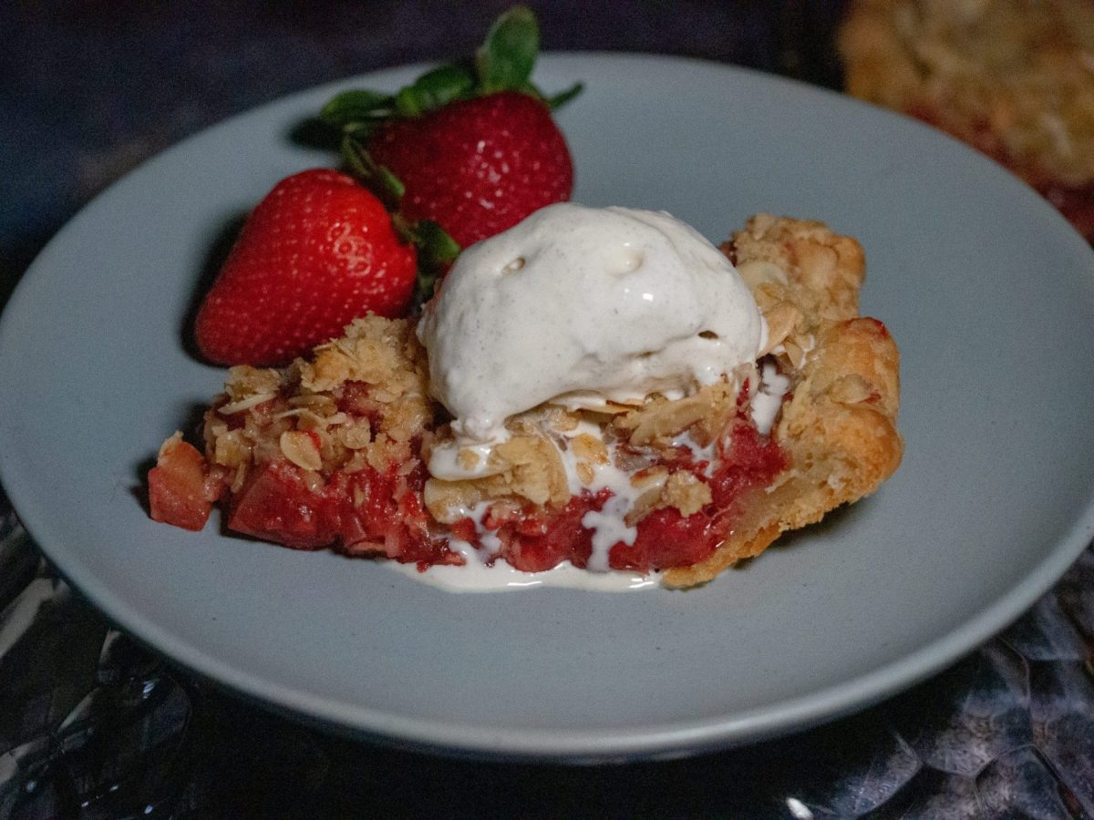 A slice of Strawberry-rhubarb pie crisp with vanilla ice cream and 2 fresh strawberries on a light blue plate