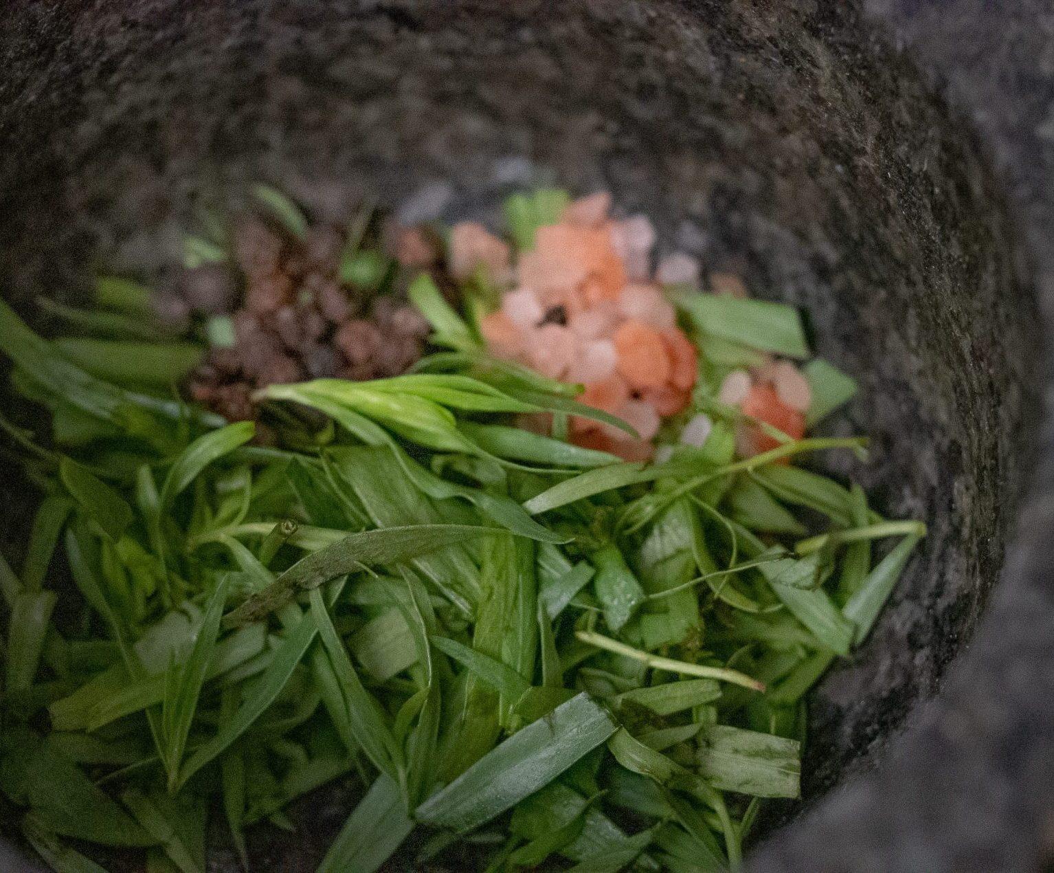 tarragon leaf, coarse pink salt and peppercorns in a grey mortar.