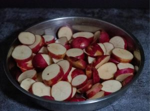 Sliced red potatoes in a stainless steel dish on top of a cement countertop