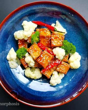 vegan chinese sesame tofu with steamed broccoli, cauliflower and toasted sesame on top