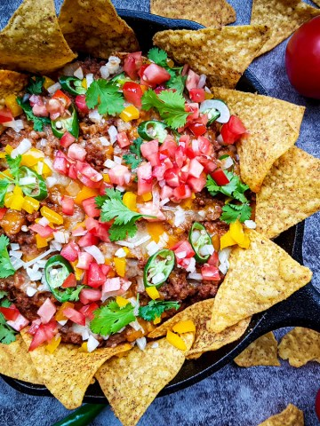 easy cheesy beef nachos recipe made with ground beef, chopped tomatoes, cilantro leaves and jalapeno