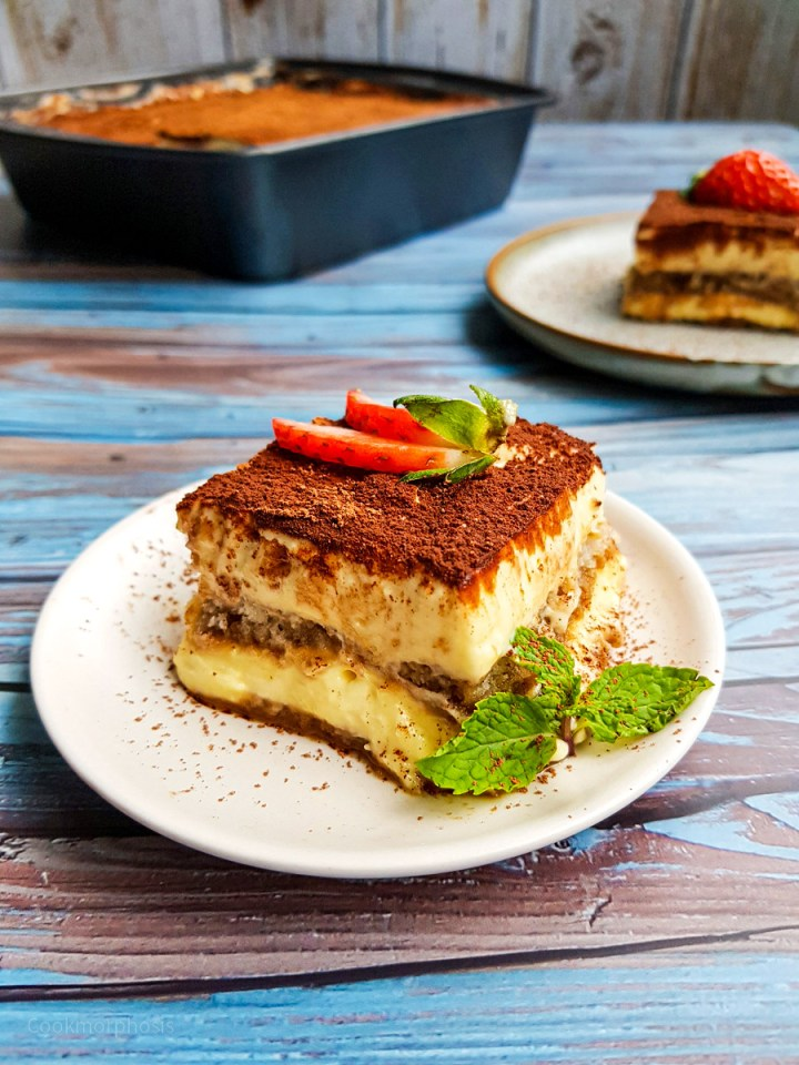 authentic tiramisu, a restaurant style dessert, is served with slices of fresh strawberries and mint leaves