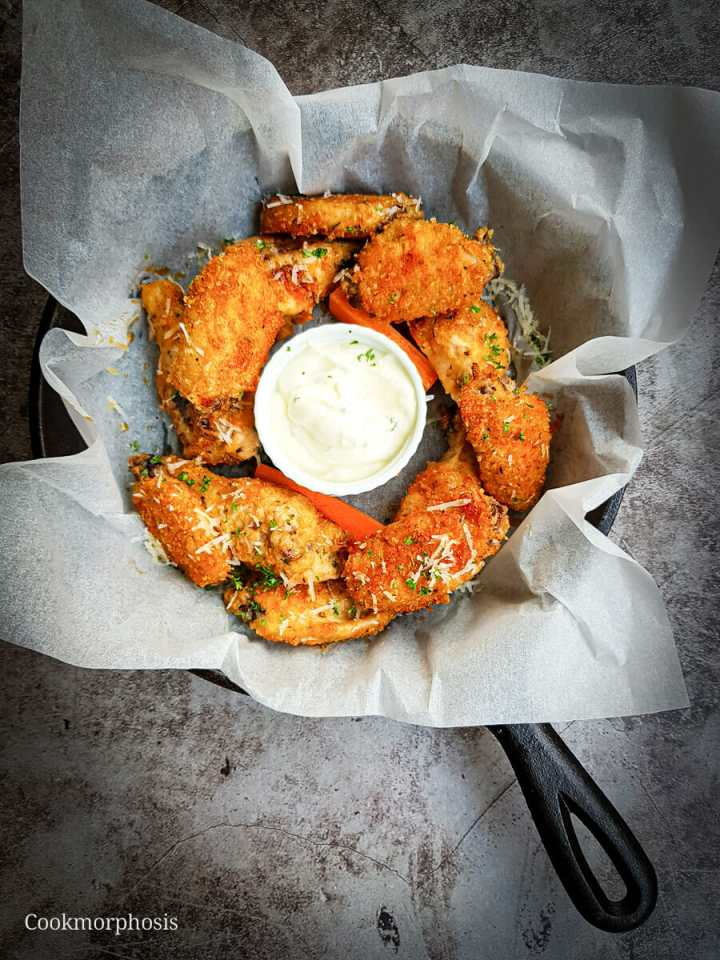 Baked parmesan chicken wings served with ranch and carrot sticks