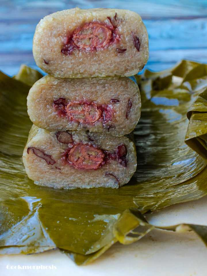 a stack of three glutinous rice banana cake slices on layers of banana leaves