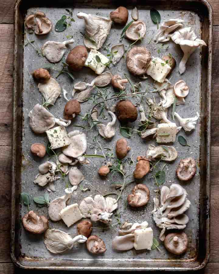 a variety of mushrooms on baking tray with butter and herbs