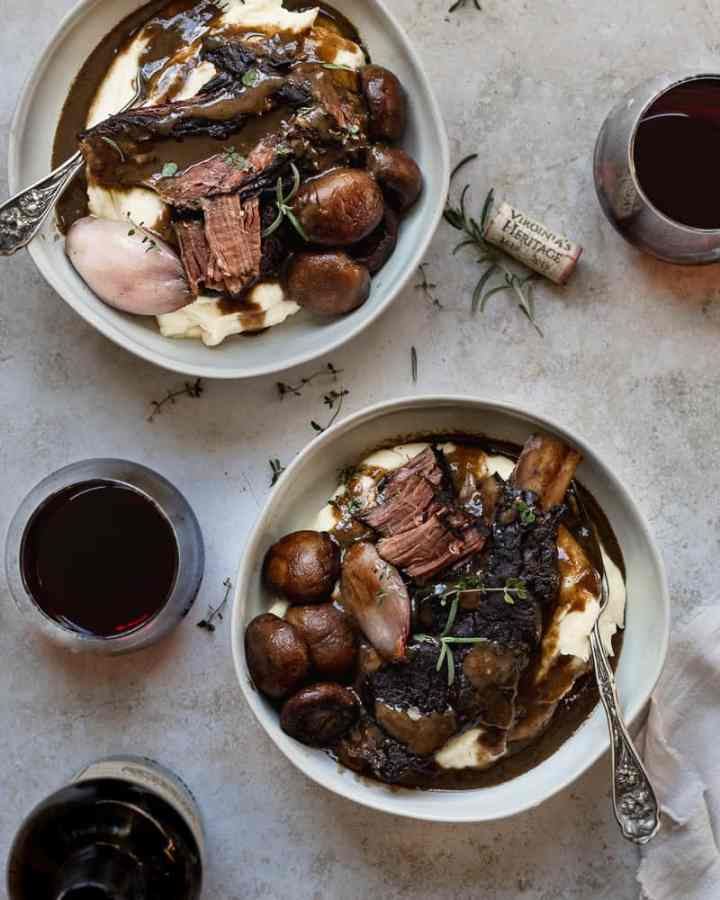 two bowls of pot roast with wine glasses and herbs scattered