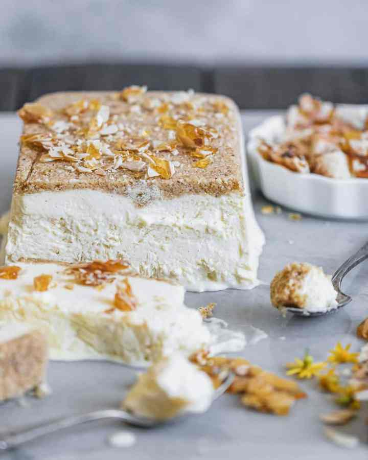 semifreddo sliced on marble surface with spoons and crumbled almond brittle