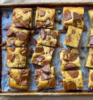 A sheet pan with Peanut Butter Blondies, embedded with Reese's peanut butter cups.