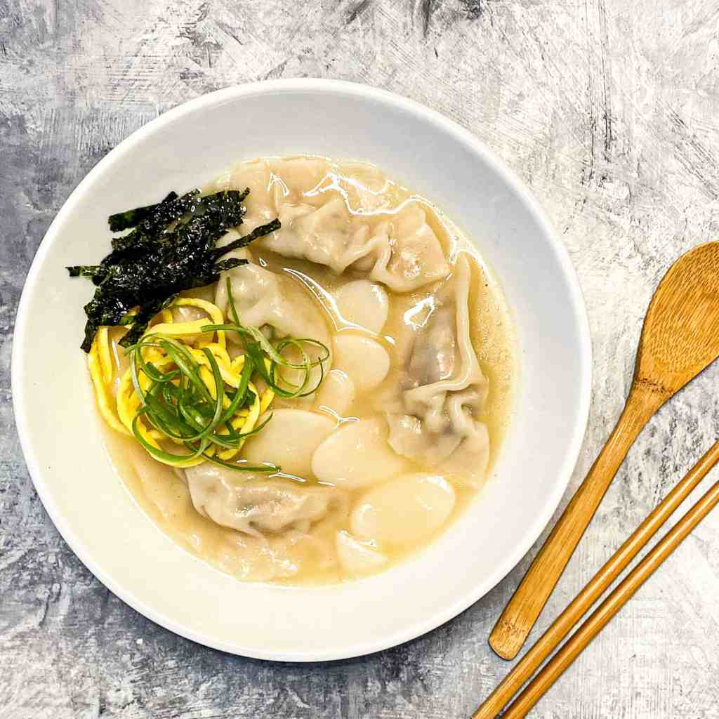 Tteok Mandu Guk (Korean Rice Cake and Dumpling Soup) in a white bowl with chopsticks and wooden spoon)