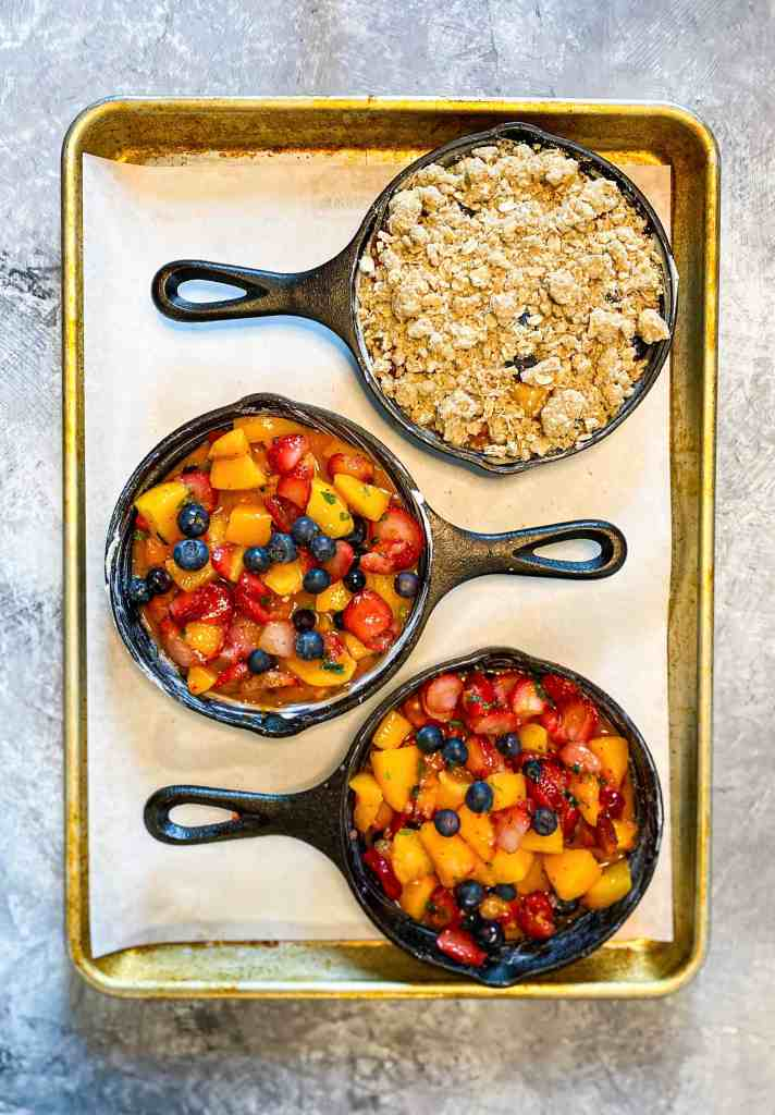 Three mini cast iron pans filled with mixed fruit, one with an oat crisp spread on top.