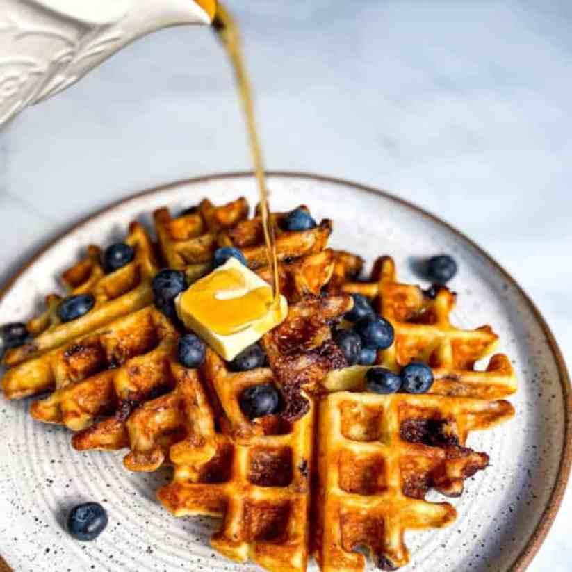 Pouring maple syrup over Lemon Ricotta Blueberry Swirl Waffles