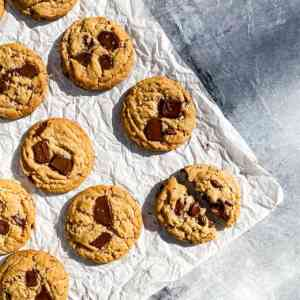 Peanut butter cookies, layered with melty chopped chocolate, laying on crumpled parchment paper