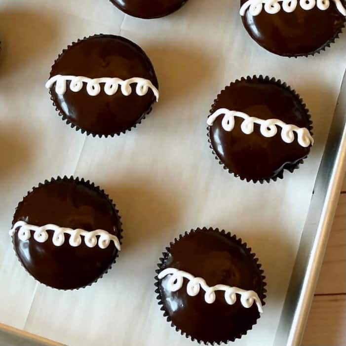 Cream Filled Chocolate Cupcakes on a parchment line sheet pan.