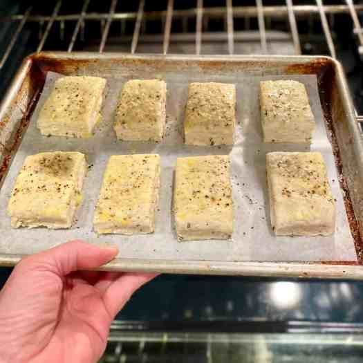 Placing a sheet tray of Rosemary Romano Cheese biscuits into the oven