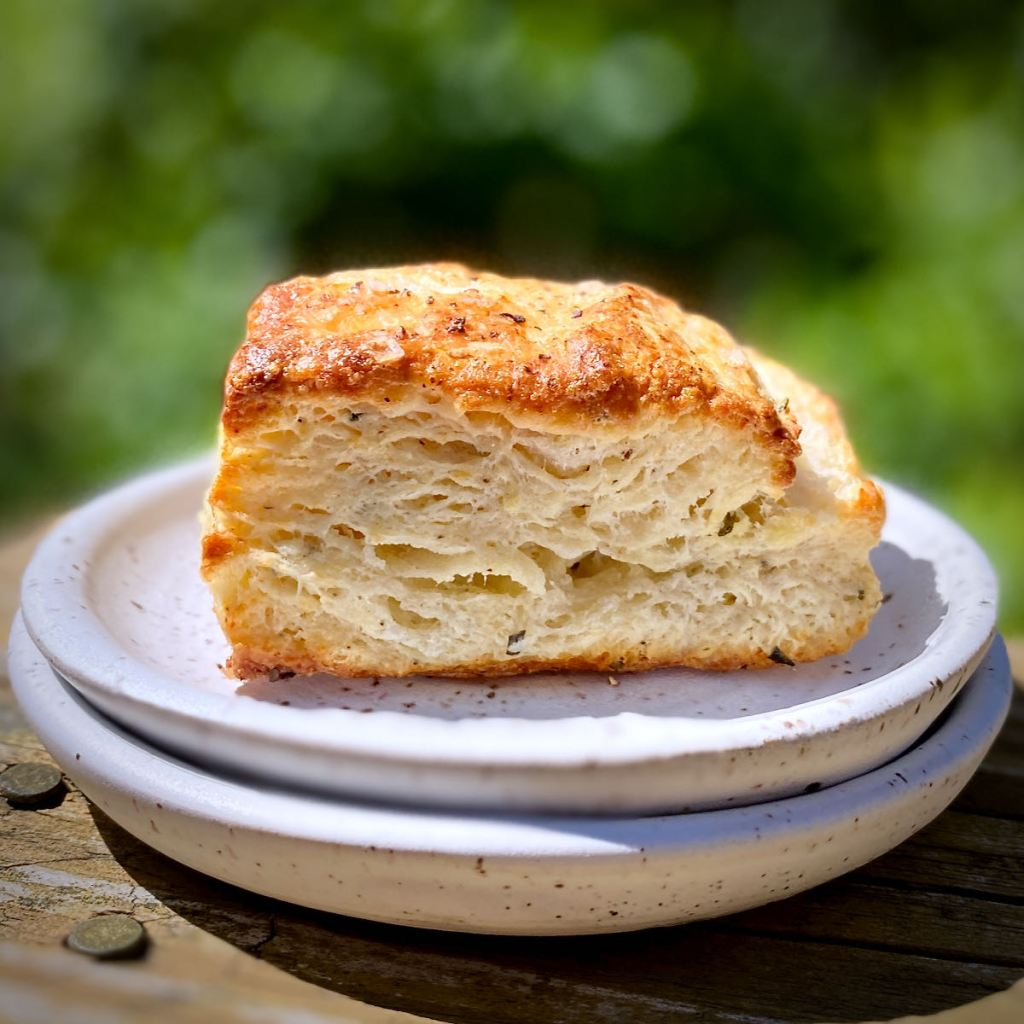 One Flaky Buttermilk Biscuit on a stack of white plates