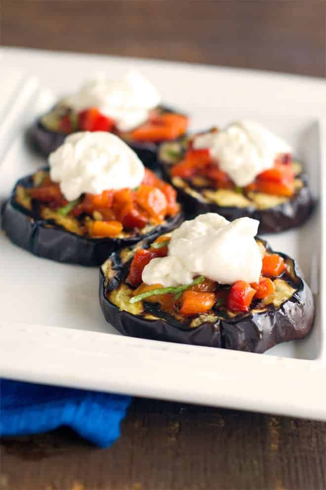 Gluten-Free Bruschetta using grilled eggplant as the base. The topping is homemade roasted peppers with garlic and basil and a big smudge of burrata cheese on top.