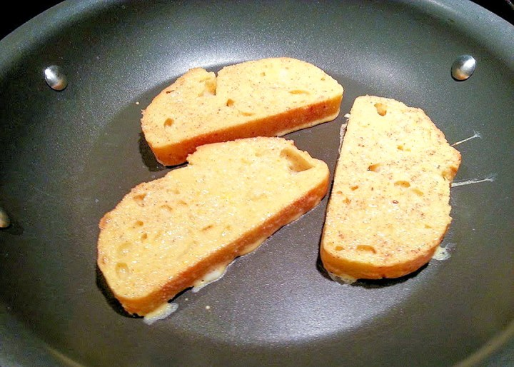 3 slices of french toast cooking in a skillet
