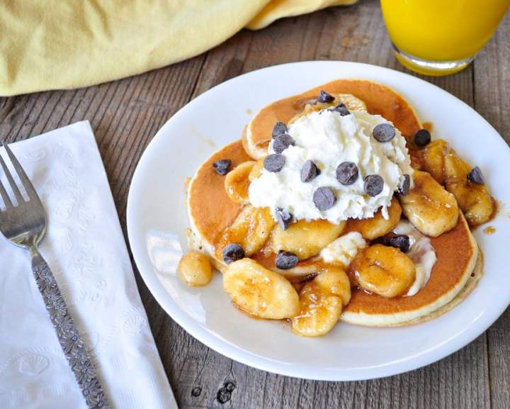 brown sugared bananas on pancakes with whipped cream and chocolate chps