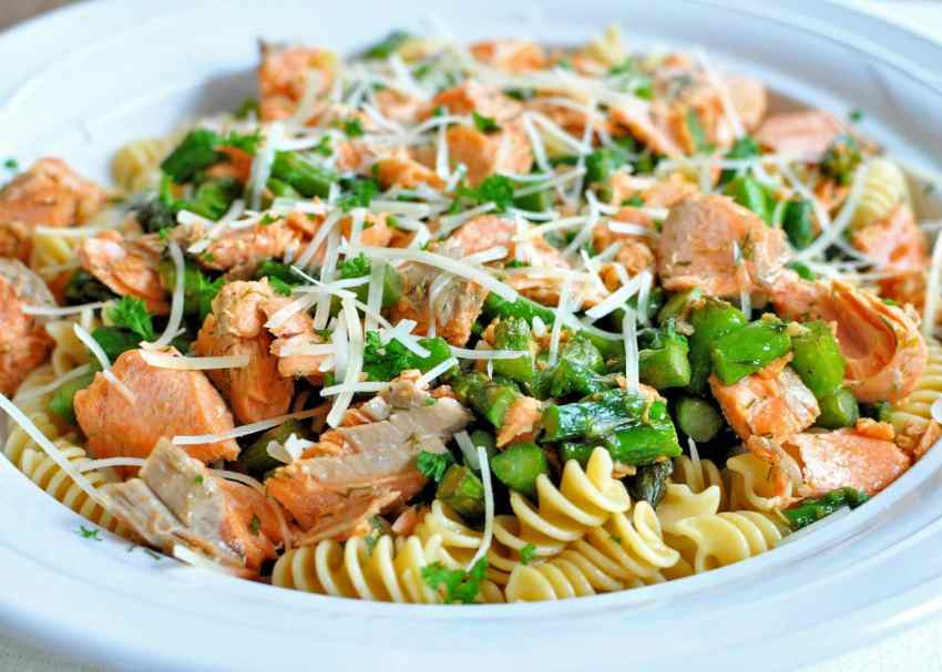 Side shot of Salmon with Pasta and Asparagus in a white bowl